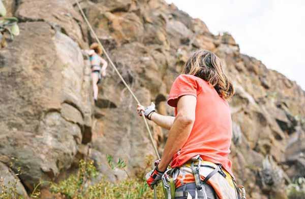 instructor ayudando a persona a escalar