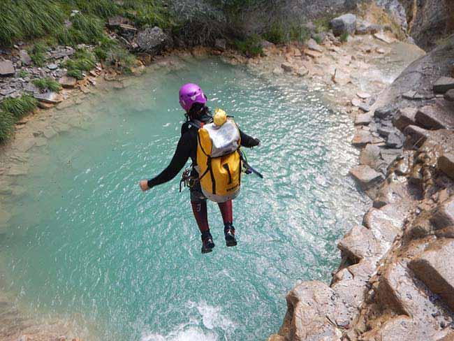 Chica saltando hacia un barranco