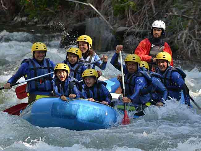 Grupo de niños haciendo rafting